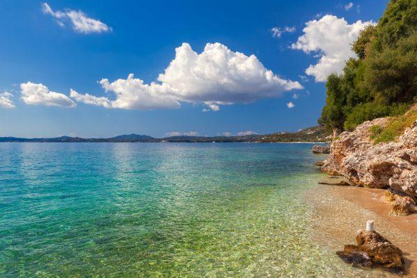 View to pebbles through transparent water at Ionian sea floor under bright sunlight near Ipsos, Corfu, Greece
